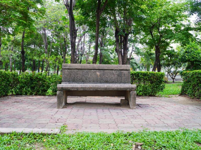 Eenzame steenbank in het groene parkmilieu stock foto's