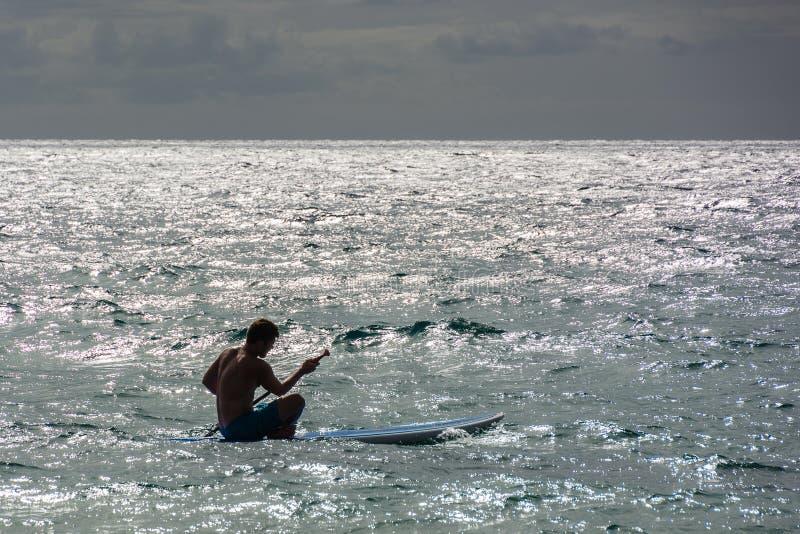 Eenzame surfer die uit aan de golven paddelen royalty-vrije stock foto
