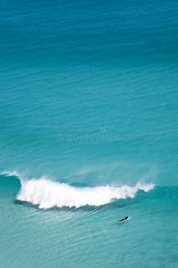 Eenzame surfer in enorme oceaan stock afbeelding