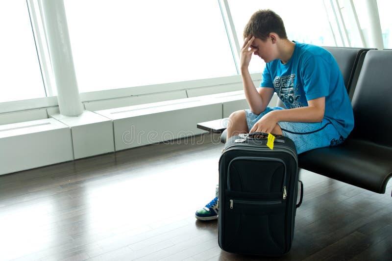 Eenzame tienerjongen bij luchthaven   stock afbeelding