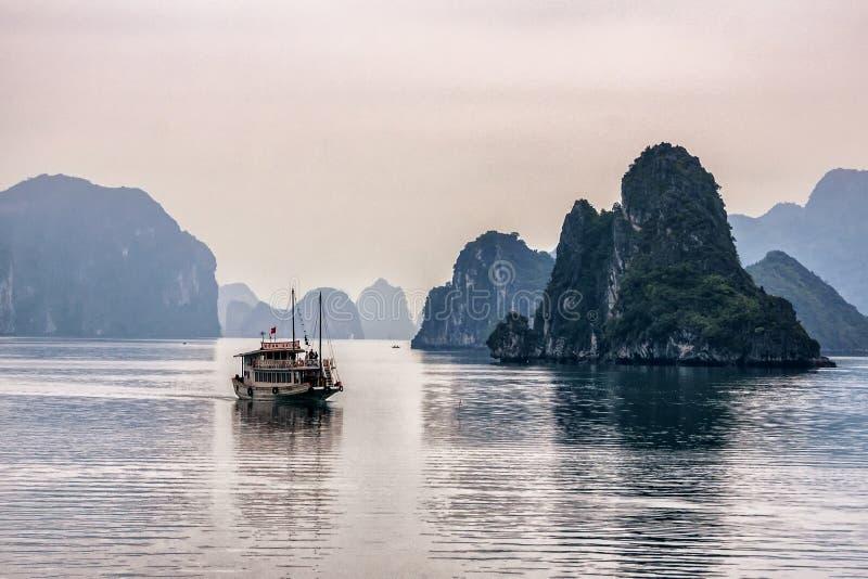 Eenzame troepboot voor kalksteenbergen stock foto's