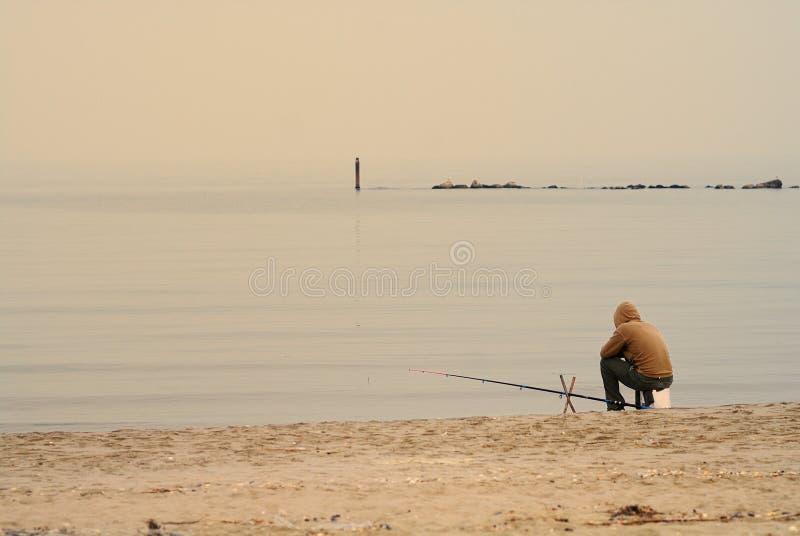 Eenzame visser op strand royalty-vrije stock fotografie