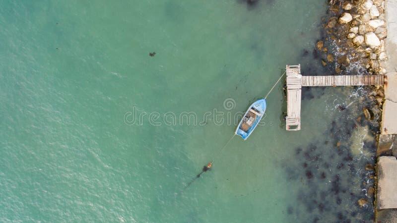 Eenzame vissersboot en houten pijler in turkooise oceaan, overzees Luchtfoto, hoogste mening stock foto