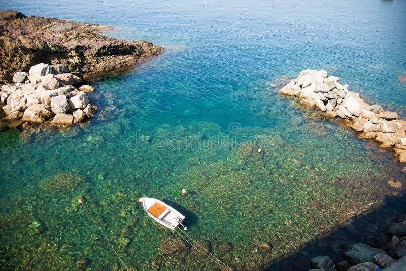 Eenzame vissersboot in Mediterrane smaragdgroene wateren stock afbeeldingen