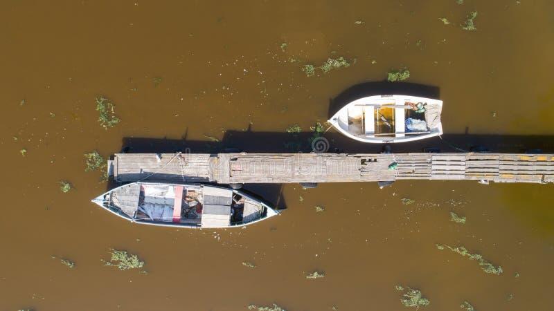 Eenzame vissersboten en houten pijler in het meer Luchtfoto, hoogste mening royalty-vrije stock afbeelding