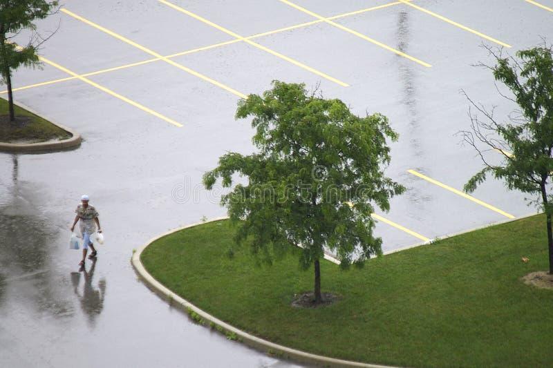 Eenzame Voetganger in Leeg Nat Parkeerterrein stock foto's