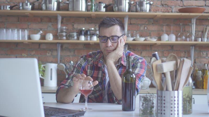 Eenzame vrijgezelmens in de keuken het drinken wijn en het bekijken witte laptop royalty-vrije stock afbeelding