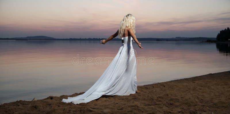 Eenzame vrouw die door de oever van het meer lopen stock fotografie