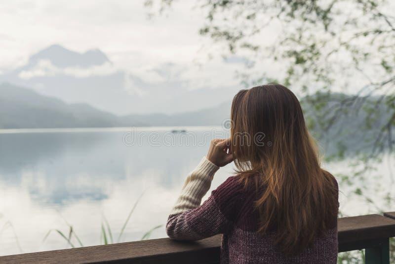 Eenzame vrouw die en zich de rivier bevinden bekijken stock fotografie