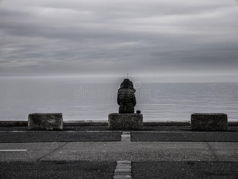 Eenzame vrouw die uit aan overzees kijken royalty-vrije stock afbeeldingen