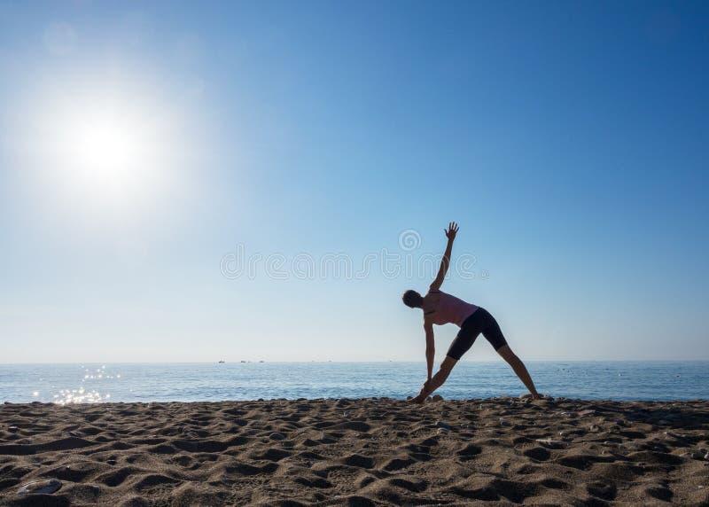Eenzame vrouw die yoga op het strand doen door oceaan op een zonnige dag, selectieve nadruk royalty-vrije stock foto's