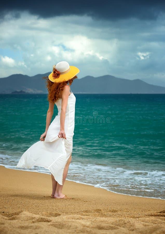 Eenzame vrouw in een witte kleding die zich bij het overzees bevinden stock fotografie