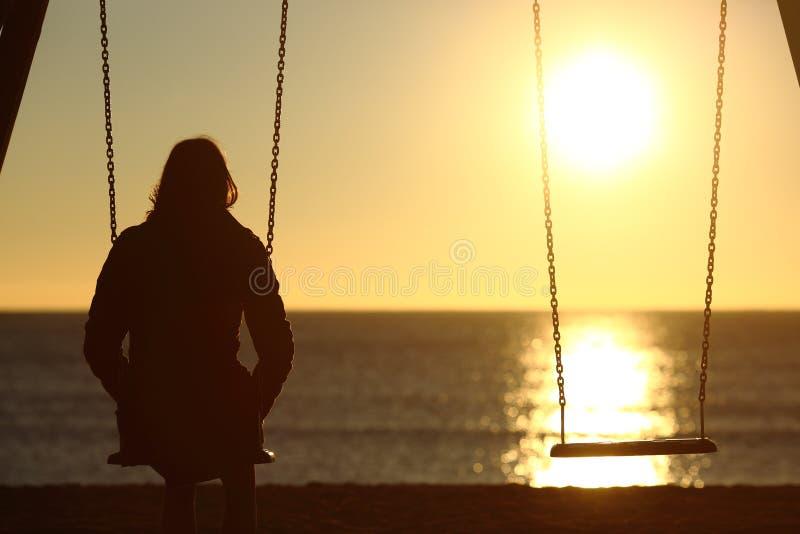 Eenzame vrouw het letten op zonsondergang alleen in de winter royalty-vrije stock foto's
