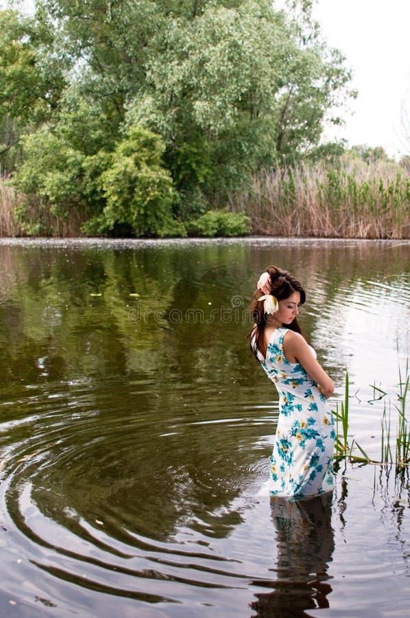 Eenzame vrouw in rivier stock foto