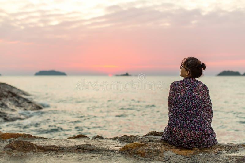 Eenzame vrouwenzitting op de kust na zonsondergang verdriet stock afbeelding