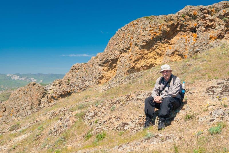 Eenzame wandelaar die korte rust op Kara -kara-dag natuurlijke reserve, de Oostelijke Krim hebben stock fotografie