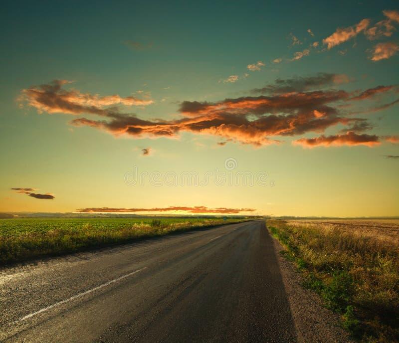 Eenzame weg die tot de horizon bij zonsonderganghemel leiden stock afbeeldingen