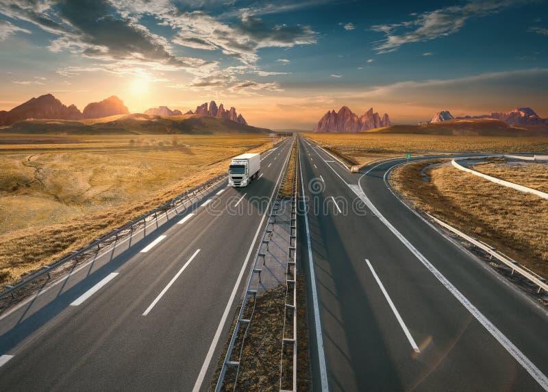 Eenzame witte vrachtwagen op weg bij idyllische zonsondergang stock afbeelding