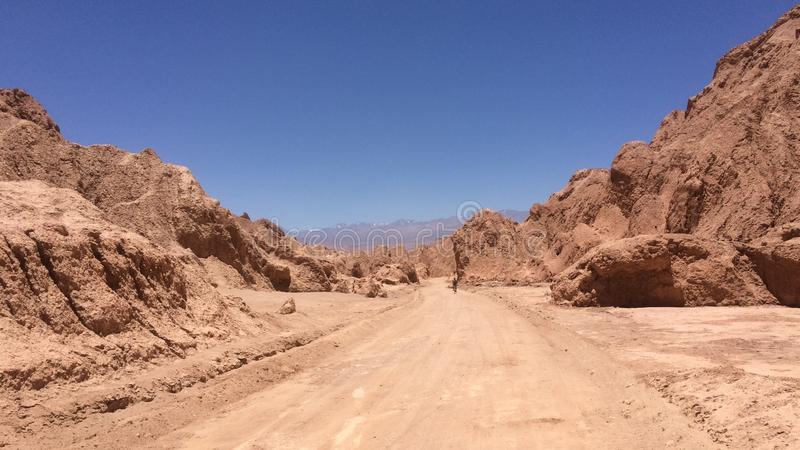 Eenzame woestijnweg die door grote rotsen winden, dichtbij San Pedro de Atacama, Chili royalty-vrije stock fotografie