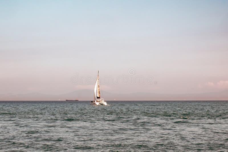 Eenzame zeilboot in open zee bij mooie zonsondergang Luxejacht die zich op de achtergrond van de schemerhemel bewegen Exotisch en stock fotografie