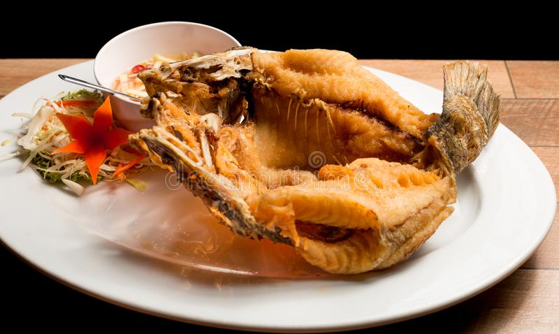 Eep fried fish with fish sauce serve with mango sauce in white dish on wood table. stock photo