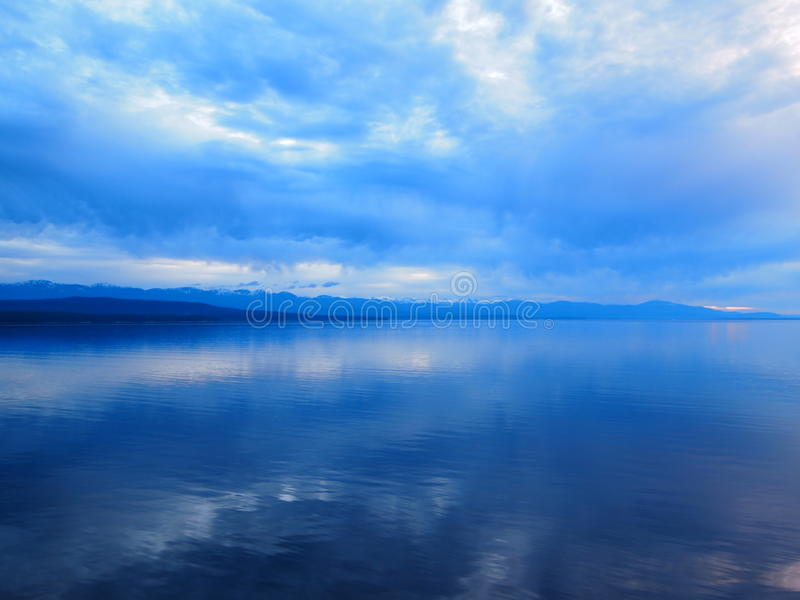 Eerie Blue Calm Waters. A dramatic blue glow creates an eerie feeling with stormy cloud cover over the calm waters of Alaska royalty free stock photography