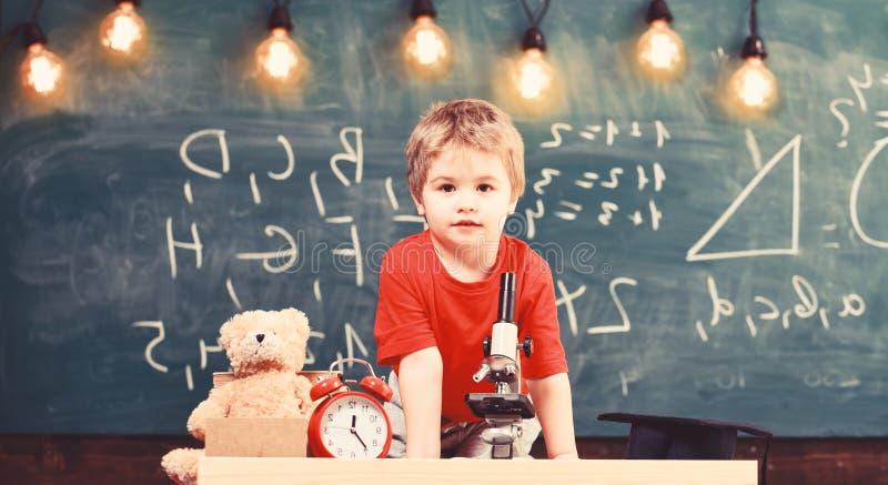 Eerst vroegere geinteresseerd in het bestuderen, het leren, onderwijs Kind op vrolijk gezicht dichtbij klok en teddybeer primair stock afbeeldingen