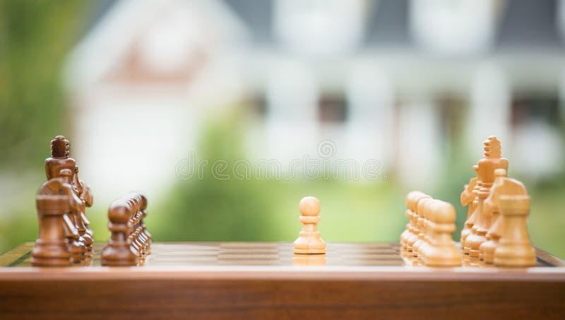 Eerste beweging over houten schaakbord Van het huisbesparingen van de onroerende goederenverkoop de leningenmarkt royalty-vrije stock foto's