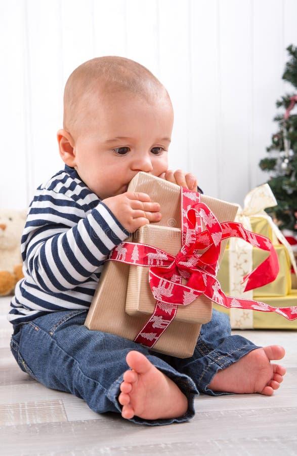 Eerste Kerstmis: blootvoetse baby die een rood heden opvouwen - leuk l stock afbeeldingen