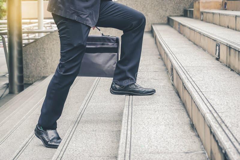 Eerste ochtend van dichte omhooggaande mening van voetzakenman die omhoog de treden in een spitsuur lopen aan het werk Haasttijd stock fotografie
