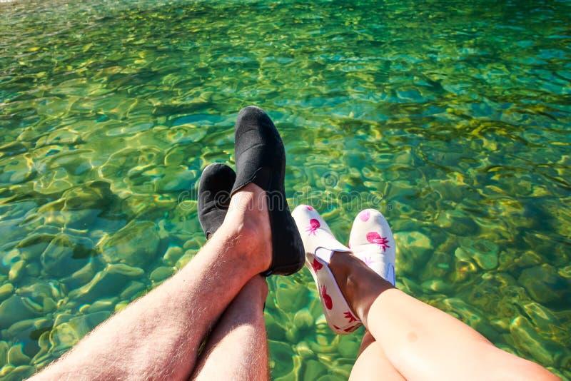 Eerste-persoonsmening over voeten van man en vrouwenzitting op klip of pijler boven het kalme duidelijke water in eiland romantis stock foto