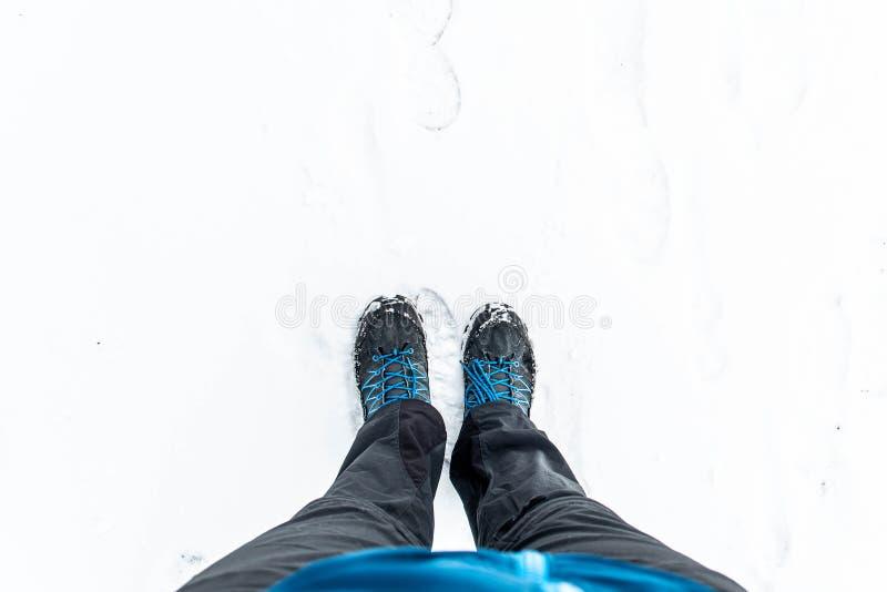 Eerste persoonsmening van benen in wandelingslaarzen in de sneeuw Sneeuw op laarzen terwijl het lopen in de winter stock afbeelding