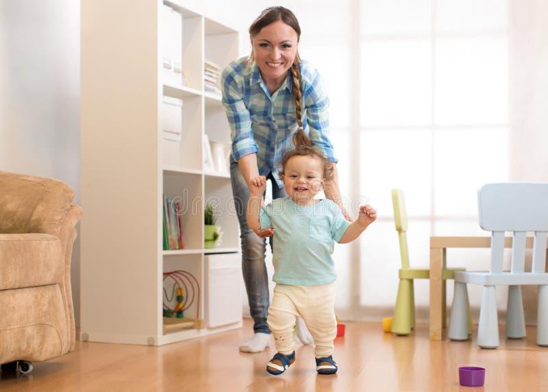 Eerste stappen van de jongen van de babypeuter het leren om in witte zonnige woonkamer te lopen Schoeisel voor kind royalty-vrije stock afbeeldingen