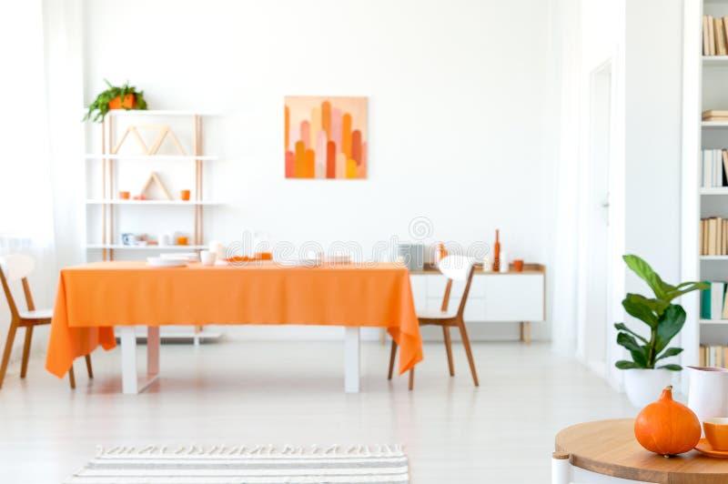 Eetkamer in levendige kleur Oranje tafelkleed op lange lijst met witte stoelen royalty-vrije stock afbeelding