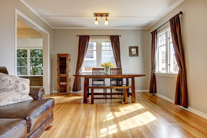 Eetkamer met bruine gordijn en hardhoutvloer. stock foto
