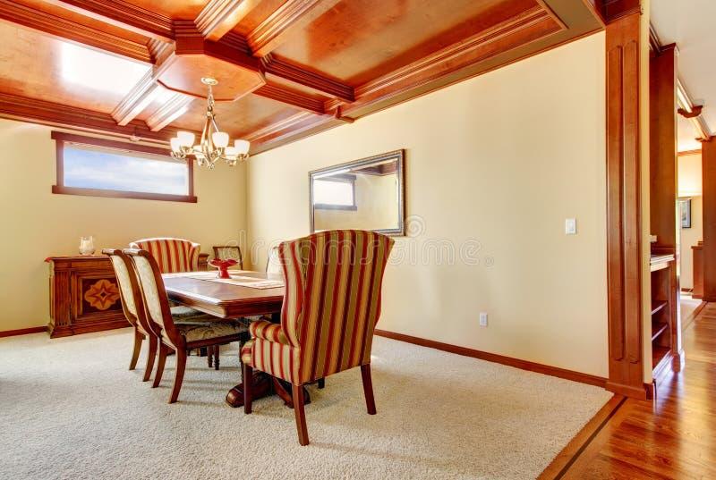Eetkamer met gele muren en houten plafond. stock foto's