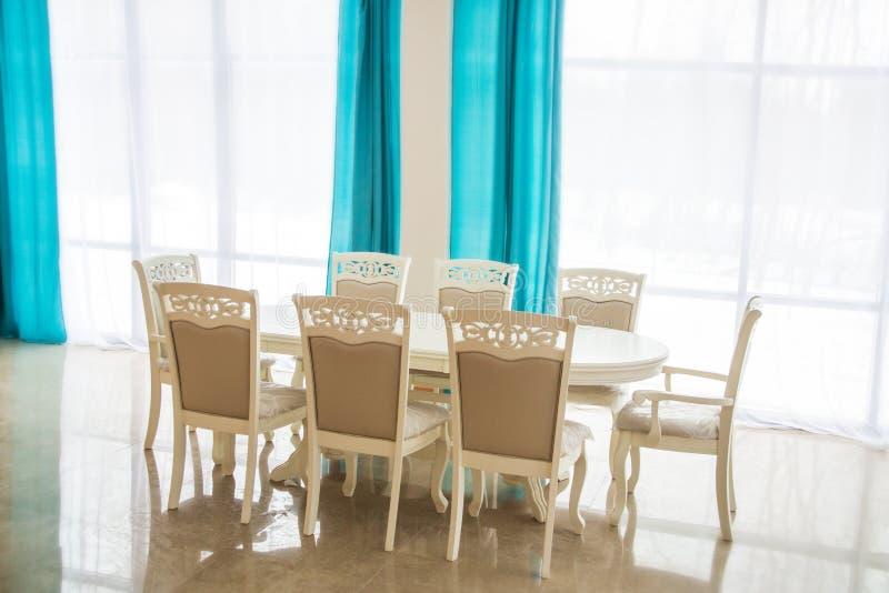 Eetkamer met houten lijst en stoelen Helder binnenland Vage achtergrond stock fotografie