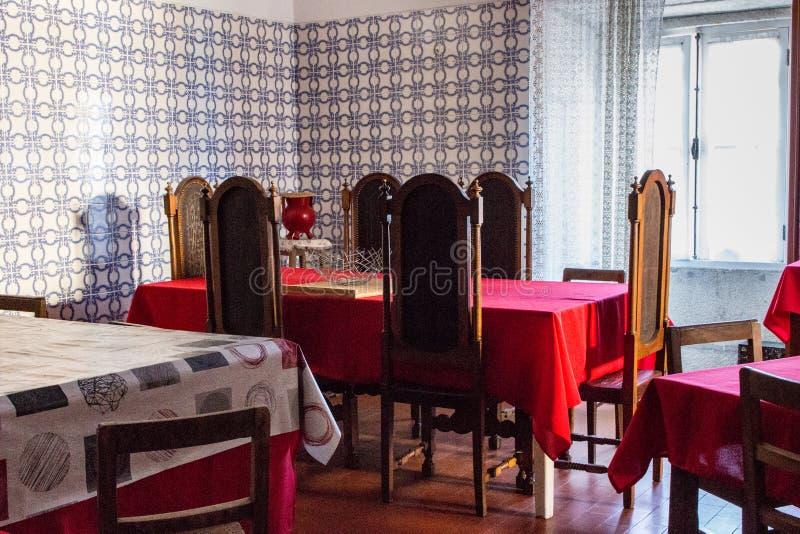 Eetkamer met rood tafelkleed en grote stoelen Eetzaal in oud klooster stock afbeeldingen