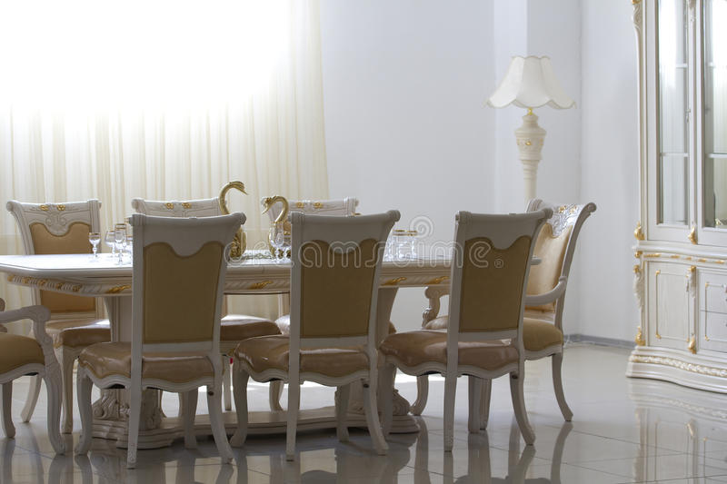 Eetkamer met wit houten meubilair.