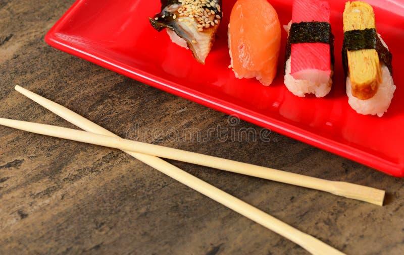 Eetstokjes dichtbij plaat met smakelijke sushi royalty-vrije stock afbeelding