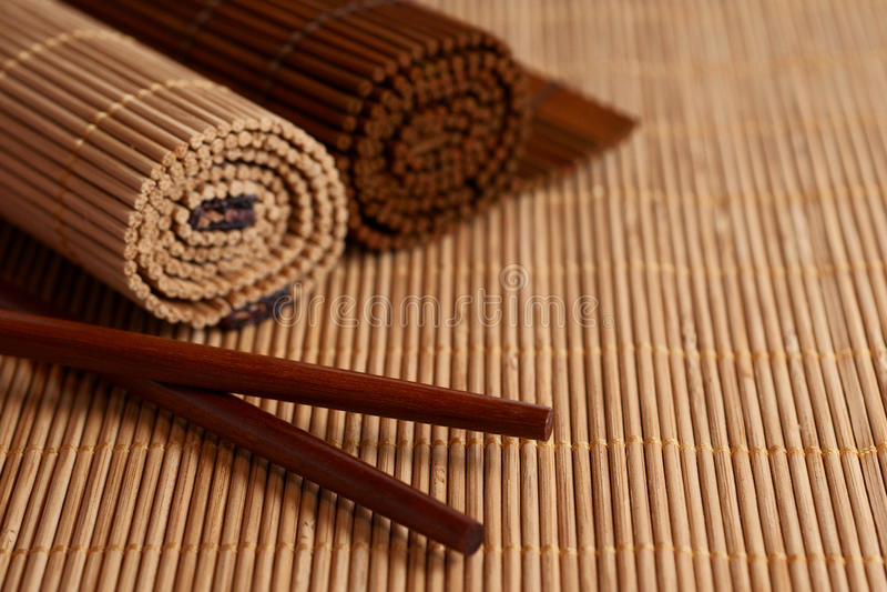 Eetstokjes en de mat van het Bamboe stock foto