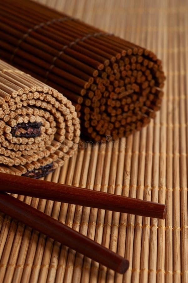 Eetstokjes en de mat van het Bamboe stock afbeelding