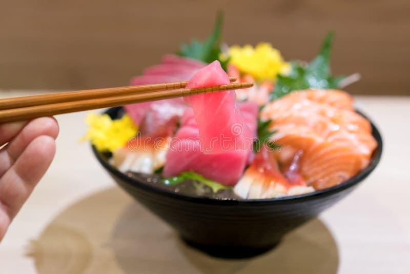 Eetstokjes met Tonijnsashimi met Gemengde gesneden vissensashimi op ijs in zwarte kom Sashimi Salmon Tuna Hamachi Prawn en Brandi stock afbeelding