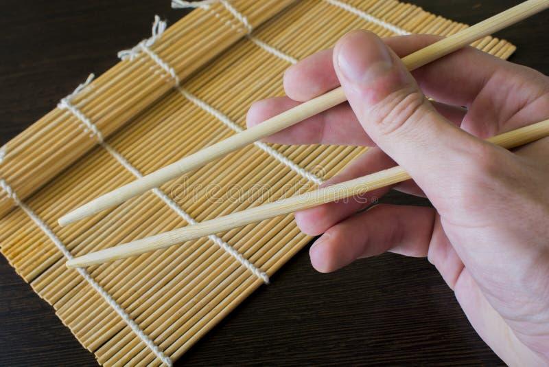 Eetstokjes ter beschikking op de achtergrond van een mat van bamboesushi royalty-vrije stock afbeelding