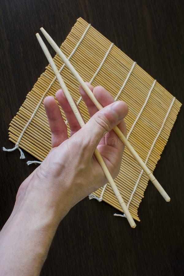 Eetstokjes ter beschikking op de achtergrond van een mat van bamboesushi stock afbeelding