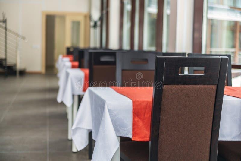Eettafels en stoelen in het restaurant Licht binnenland stock fotografie