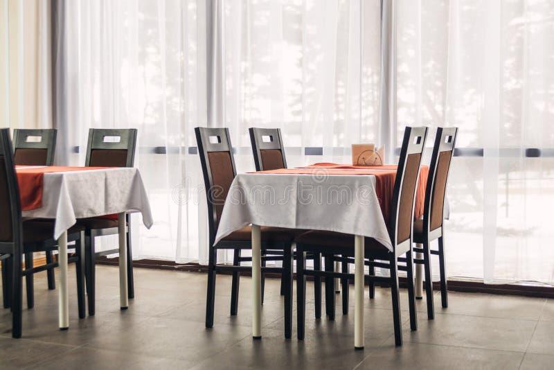 Eettafels en stoelen in het restaurant Licht binnenland royalty-vrije stock foto