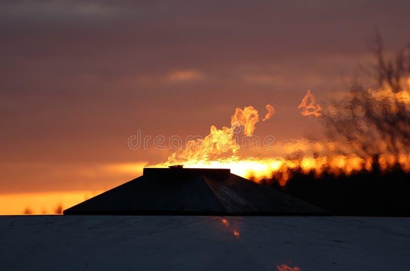 Eeuwig Vlamgedenkteken aan slachtoffers van Wereldoorlog II bij zonsondergang stock afbeelding
