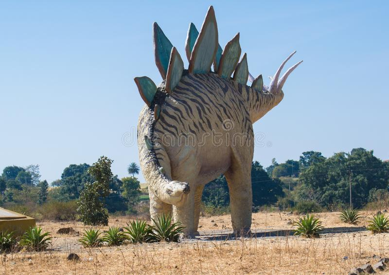 Efígie ou escultura do Stegosaurus do dinossauro na floresta foto de stock