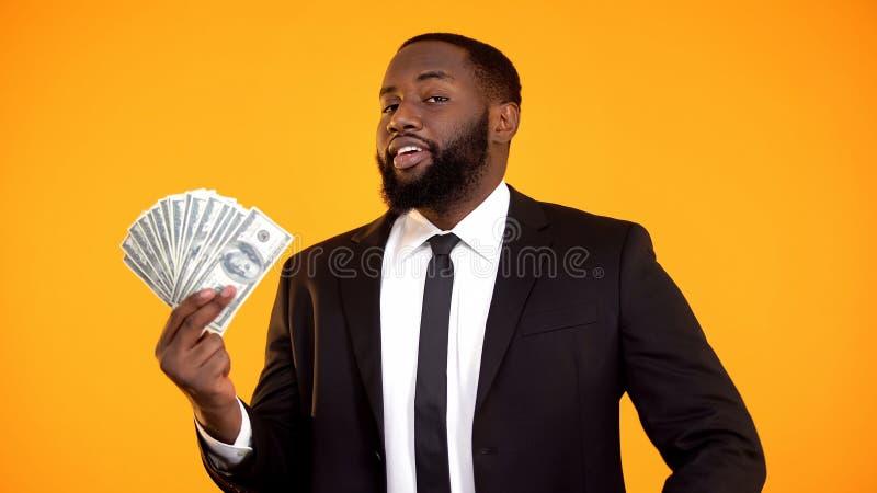 Efectivo afroamericano satisfecho seguro de s? mismo del d?lar de la demostraci?n del hombre de negocios, renta fotos de archivo libres de regalías